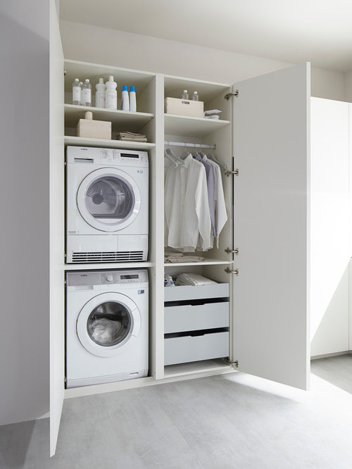 Minimalist laundry room photo in Other with white cabinets, white walls and  a stacked washer