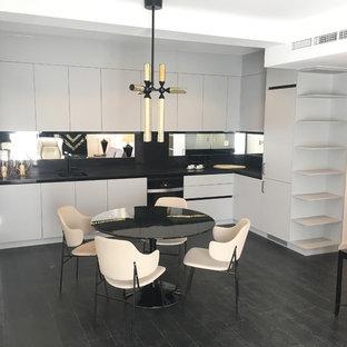 Immagine di una grande cucina moderna con lavello sottopiano, ante lisce, ante grigie, top in quarzo composito, paraspruzzi a specchio, elettrodomestici neri, parquet scuro, nessuna isola e pavimento nero