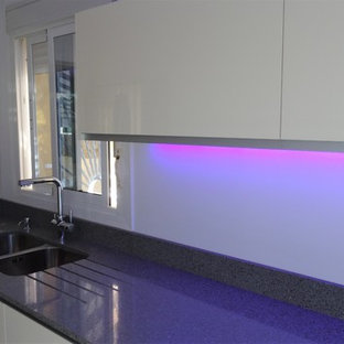Diseño de cocina lineal, moderna, abierta, con fregadero bajoencimera, armarios con paneles lisos, encimera de cuarzo compacto, electrodomésticos de acero inoxidable, una isla y encimeras grises