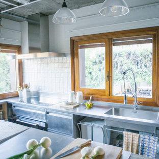 Imagen de cocina en L, industrial, grande, abierta, con armarios con paneles lisos, puertas de armario en acero inoxidable, encimera de acero inoxidable y una isla