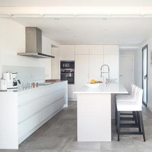 マドリードの大きい地中海スタイルのおしゃれなキッチン (アンダーカウンターシンク、フラットパネル扉のキャビネット、白いキャビネット、クオーツストーンカウンター、白いキッチンパネル、ガラスまたは窓のキッチンパネル、パネルと同色の調理設備、セラミックタイルの床、グレーの床、白いキッチンカウンター) の写真
