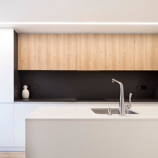 This is an example of a mid-sized modern single-wall open plan kitchen in Valencia with an integrated sink, metallic splashback, brown floor, beige benchtop, flat-panel cabinets, white cabinets, marble benchtops, metal splashback, with island and laminate floors.