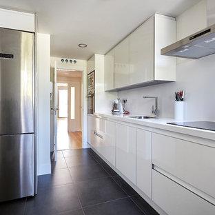 Diseño de cocina lineal, moderna, de tamaño medio, cerrada, sin isla, con armarios con paneles lisos, puertas de armario blancas, salpicadero blanco, electrodomésticos de acero inoxidable, encimeras blancas, fregadero bajoencimera, suelo negro y suelo de cemento