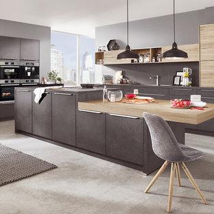 マドリードの中サイズのモダンスタイルのおしゃれなキッチン (一体型シンク、落し込みパネル扉のキャビネット、淡色木目調キャビネット、ラミネートカウンター、グレーのキッチンパネル、トラバーチンの床、シルバーの調理設備の、トラバーチンの床、グレーの床、グレーのキッチンカウンター) の写真
