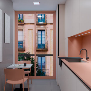 他の地域の中くらいのモダンスタイルのおしゃれなキッチン (アンダーカウンターシンク、フラットパネル扉のキャビネット、白いキャビネット、ソープストーンカウンター、ピンクのキッチンパネル、クオーツストーンのキッチンパネル、シルバーの調理設備、セメントタイルの床、アイランドなし、グレーの床、ピンクのキッチンカウンター、折り上げ天井) の写真