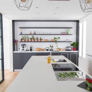 Imagen de cocina contemporánea, grande, cerrada, con puertas de armario blancas, encimera de cuarzo compacto, una isla, encimeras blancas, fregadero bajoencimera, armarios con paneles lisos, suelo de madera clara y suelo beige