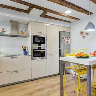 Design ideas for a small eclectic l-shaped open plan kitchen in Madrid with flat-panel cabinets, beige cabinets, white splashback, stainless steel appliances, light hardwood floors, beige floor and beige benchtop.