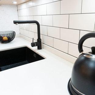 Esempio di una cucina a L moderna chiusa e di medie dimensioni con lavello stile country, ante bianche, top piastrellato, paraspruzzi nero, elettrodomestici neri, pavimento con piastrelle in ceramica, penisola, pavimento marrone e top bianco