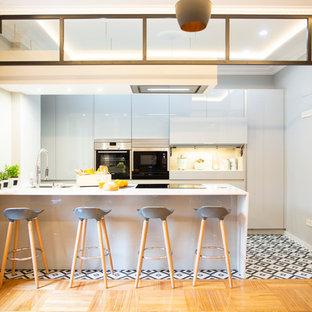 Imagen de cocina comedor lineal, contemporánea, grande, con fregadero de doble seno, puertas de armario grises, salpicadero metalizado, electrodomésticos de acero inoxidable, suelo de baldosas de cerámica, una isla, suelo multicolor y encimeras blancas