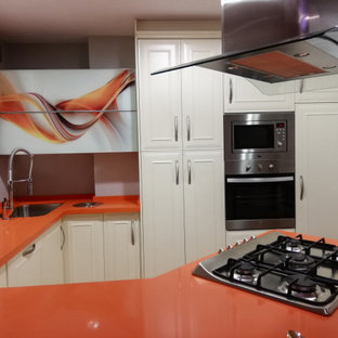 Photo of a small traditional u-shaped eat-in kitchen in Malaga with an undermount sink, beaded inset cabinets, white cabinets, quartz benchtops, stainless steel appliances, terrazzo floors, a peninsula, multi-coloured floor and orange benchtop.