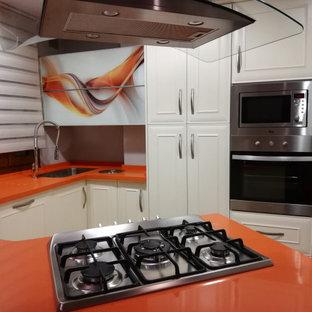 Modelo de cocina comedor en U, tradicional, pequeña, con fregadero bajoencimera, armarios con rebordes decorativos, puertas de armario blancas, encimera de cuarzo compacto, electrodomésticos de acero inoxidable, suelo de terrazo, península, suelo multicolor y encimeras naranjas