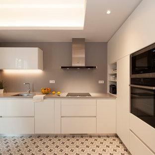 バルセロナの広いモダンスタイルのおしゃれなキッチン (シングルシンク、フラットパネル扉のキャビネット、白いキャビネット、クオーツストーンカウンター、グレーのキッチンパネル、黒い調理設備、セラミックタイルの床、アイランドなし、マルチカラーの床) の写真