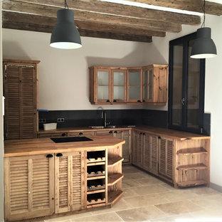 トゥールーズの中サイズのラスティックスタイルのおしゃれなキッチン (ダブルシンク、ルーバー扉のキャビネット、中間色木目調キャビネット、木材カウンター、グレーのキッチンパネル、大理石のキッチンパネル、パネルと同色の調理設備、茶色い床) の写真