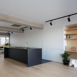 Imagen de cocina lineal, minimalista, abierta, con fregadero encastrado, armarios con paneles lisos, puertas de armario blancas, encimera de granito, electrodomésticos negros, suelo de madera clara, una isla, encimeras negras y suelo beige