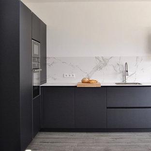 Modelo de cocina en L, minimalista, sin isla, con armarios con paneles lisos, puertas de armario negras, salpicadero blanco, encimeras blancas, fregadero de un seno, electrodomésticos con paneles y suelo gris