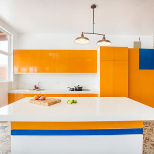 Photo of a contemporary galley kitchen in Other with an undermount sink, flat-panel cabinets, orange cabinets, white splashback, panelled appliances, with island, multi-coloured floor and white benchtop.