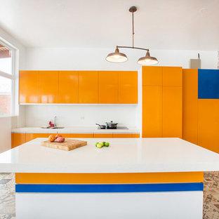 Modern inredning av ett vit vitt parallellkök, med en undermonterad diskho, släta luckor, orange skåp, vitt stänkskydd, integrerade vitvaror, en köksö och flerfärgat golv