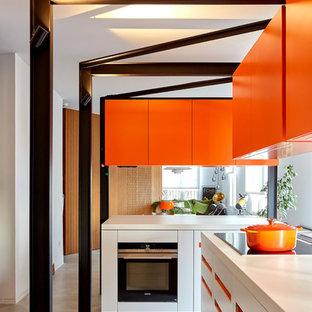 Réalisation d'une grande cuisine ouverte minimaliste en U avec un évier encastré, un placard à porte plane, un électroménager encastrable, béton au sol, un îlot central, un sol gris et un plan de travail blanc.