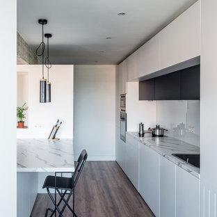 マドリードの大きいインダストリアルスタイルのおしゃれなキッチン (エプロンフロントシンク、フラットパネル扉のキャビネット、白いキャビネット、ラミネートカウンター、白いキッチンパネル、ガラスまたは窓のキッチンパネル、パネルと同色の調理設備、無垢フローリング、茶色い床、白いキッチンカウンター) の写真