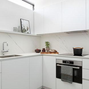 Modelo de cocina en L, actual, con fregadero bajoencimera, armarios con paneles lisos, puertas de armario blancas, salpicadero blanco, salpicadero de losas de piedra, electrodomésticos de acero inoxidable, suelo multicolor y encimeras blancas