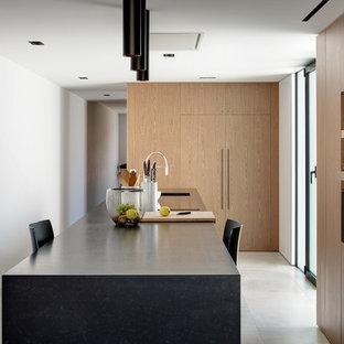 Foto de cocina contemporánea, abierta, con fregadero de un seno, armarios con paneles lisos, puertas de armario de madera en tonos medios, encimera de granito, electrodomésticos negros, suelo de baldosas de porcelana, una isla, suelo gris y encimeras negras
