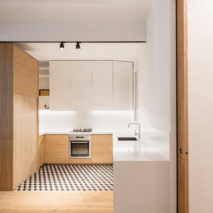 This is an example of a mid-sized scandinavian u-shaped kitchen in Barcelona with flat-panel cabinets, white splashback, stainless steel appliances, ceramic floors, no island, multi-coloured floor, a single-bowl sink and white cabinets.