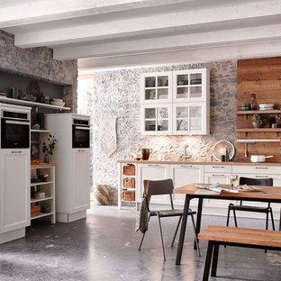 Diseño de cocina nórdica, abierta, con puertas de armario blancas, encimera de madera y salpicadero de madera