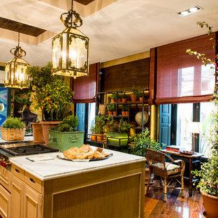 マドリードの中くらいのトロピカルスタイルのおしゃれなキッチン (レイズドパネル扉のキャビネット、中間色木目調キャビネット) の写真