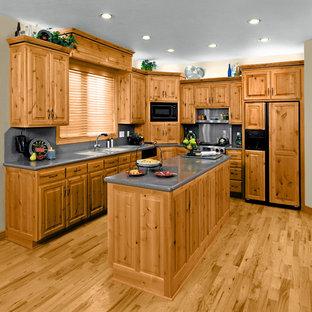 Geschlossene, Mittelgroße Country Küche in L-Form mit Doppelwaschbecken, Schrankfronten mit vertiefter Füllung, hellbraunen Holzschränken, Küchengeräten aus Edelstahl, braunem Holzboden und Kücheninsel in Madrid