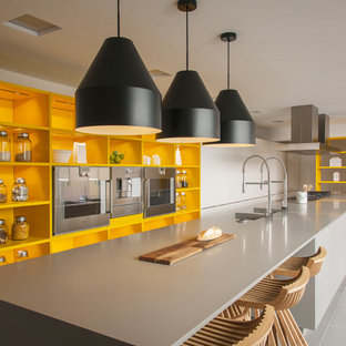 Large contemporary kitchen designs - Example of a large trendy single-wall gray floor kitchen design in Barcelona with open cabinets, yellow cabinets, an island and stainless steel appliances