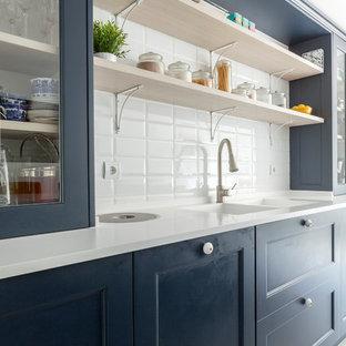 Diseño de cocina clásica renovada con puertas de armario azules, salpicadero blanco, encimeras blancas, fregadero de doble seno y armarios tipo vitrina