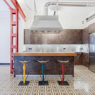 他の地域の大きいインダストリアルスタイルのおしゃれなキッチン (フラットパネル扉のキャビネット、茶色いキャビネット、シルバーの調理設備の、メタリックのキッチンパネル) の写真