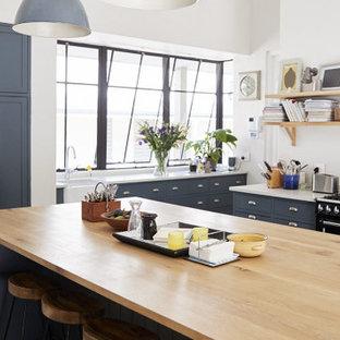 Ejemplo de cocina en U, tradicional renovada, extra grande, con fregadero sobremueble, armarios con paneles lisos, puertas de armario azules, salpicadero de vidrio, electrodomésticos de acero inoxidable, una isla, suelo gris y encimeras blancas