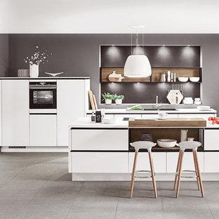 Idéer för små funkis vitt kök, med en integrerad diskho, luckor med infälld panel, svarta vitvaror, en köksö, grått golv, vita skåp, bänkskiva i koppar, vitt stänkskydd, stänkskydd i stickkakel och klinkergolv i keramik
