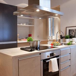 Ejemplo de cocina de galera, clásica renovada, pequeña, cerrada, con fregadero encastrado, armarios con paneles lisos, puertas de armario grises, encimera de acrílico, electrodomésticos de acero inoxidable, suelo de madera clara y una isla