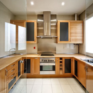Photo of a mid-sized scandinavian u-shaped separate kitchen in Madrid with a drop-in sink, shaker cabinets, medium wood cabinets, wood benchtops, metallic splashback, metal splashback, no island, stainless steel appliances and ceramic floors.