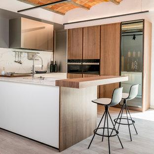 Imagen de cocina en L, contemporánea, de tamaño medio, abierta, con armarios con paneles lisos, puertas de armario de madera oscura, encimera de mármol, electrodomésticos de acero inoxidable, suelo de madera clara y península