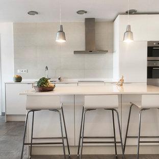 Ejemplo de cocina lineal, contemporánea, de tamaño medio, abierta, con armarios con paneles lisos, puertas de armario blancas, salpicadero blanco, electrodomésticos de acero inoxidable, una isla, suelo gris y encimeras blancas