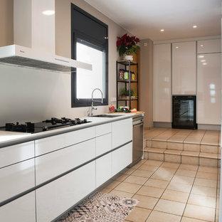 Diseño de cocina en U, contemporánea, sin isla, con fregadero bajoencimera, armarios con paneles lisos, puertas de armario blancas, electrodomésticos de acero inoxidable, encimeras blancas, salpicadero blanco y suelo beige