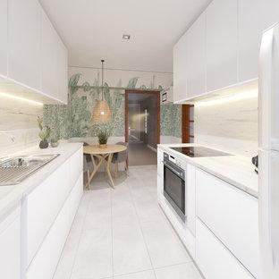 Inredning av ett modernt vit vitt kök, med släta luckor, vita skåp, en nedsänkt diskho, beige stänkskydd och vitt golv