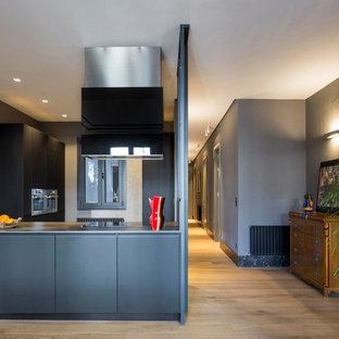 Ejemplo de cocina contemporánea, de tamaño medio, abierta, con armarios con paneles lisos, puertas de armario negras, electrodomésticos de acero inoxidable, península y suelo de madera clara