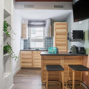 Ejemplo de cocina comedor lineal, escandinava, de tamaño medio, con puertas de armario de madera clara, salpicadero azul, salpicadero de azulejos de cerámica, una isla y encimeras negras