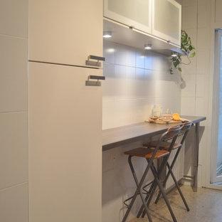 Modelo de cocina lineal, contemporánea, pequeña, sin isla, con despensa, armarios con paneles lisos, puertas de armario blancas, encimera de laminado, salpicadero blanco, salpicadero de azulejos de cerámica y suelo de terrazo
