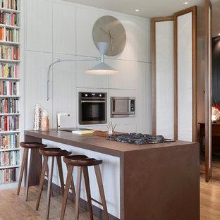Ejemplo de cocina lineal, actual, abierta, con armarios con paneles lisos, puertas de armario blancas, suelo de madera clara, suelo beige y una isla