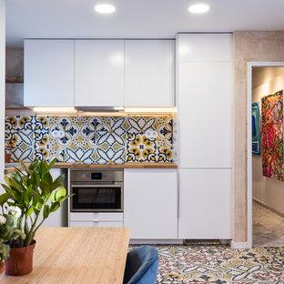 Diseño de cocina comedor en L, actual, pequeña, sin isla, con armarios con paneles lisos, puertas de armario blancas, encimera de madera, electrodomésticos de acero inoxidable, fregadero encastrado, salpicadero multicolor, suelo multicolor y encimeras beige