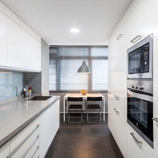Diseño de cocina de galera, actual, grande, cerrada, sin isla, con fregadero bajoencimera, armarios con paneles lisos, puertas de armario blancas, electrodomésticos de acero inoxidable, suelo gris, encimeras grises, salpicadero verde y salpicadero de vidrio templado