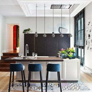Diseño de cocina de galera, actual, abierta, con armarios con paneles lisos, puertas de armario negras, encimera de madera, suelo de madera clara y una isla