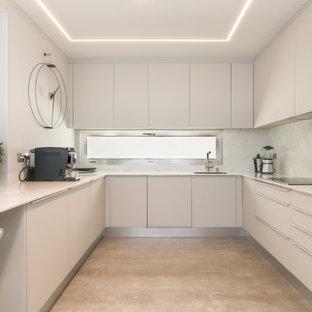 Diseño de cocina en U, contemporánea, de tamaño medio, con fregadero bajoencimera, armarios con paneles lisos, puertas de armario blancas, salpicadero blanco, electrodomésticos de acero inoxidable, suelo de baldosas de porcelana, península, suelo gris y encimeras blancas