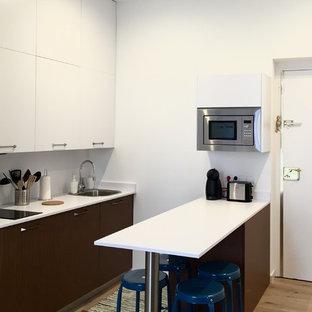 Modelo de cocina actual con armarios con paneles lisos, península, encimeras blancas, fregadero de un seno, puertas de armario blancas, salpicadero blanco, electrodomésticos de acero inoxidable y suelo de madera clara
