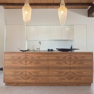 Ejemplo de cocina lineal, contemporánea, de tamaño medio, abierta, con armarios con paneles lisos, puertas de armario blancas y una isla